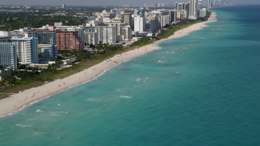 5K stock footage aerial video tilt from the ocean to reveal beachfront condos in Miami Beach, Florida Aerial Stock Footage | AX0020_056