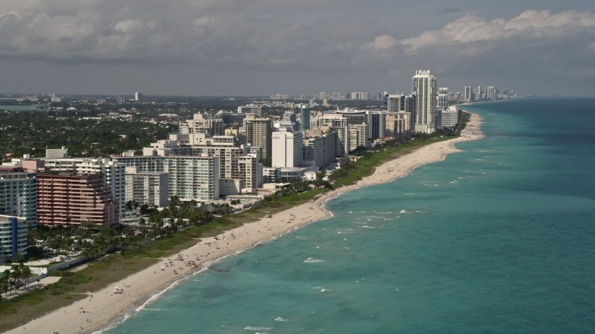 5K stock footage aerial video tilt from the ocean to reveal beachfront condos in Miami Beach, Florida Aerial Stock Footage | AX0020_056E