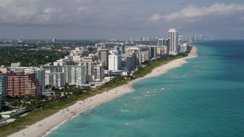 5K stock footage aerial video approach beachfront condominiums lining the coast in Miami Beach, Florida Aerial Stock Footage   AX0020_057
