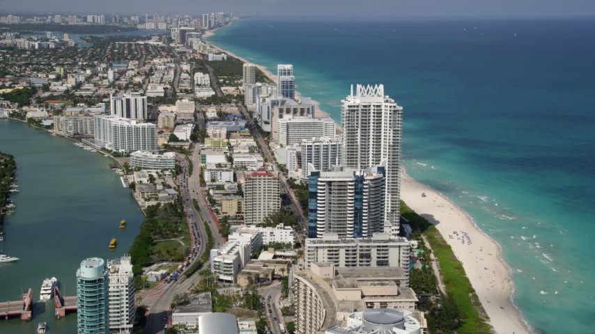 5K aerial video follow Indian Creek Drive by beachfront condo complexes and hotels in Miami Beach, Florida Aerial Stock Footage | AX0020_060