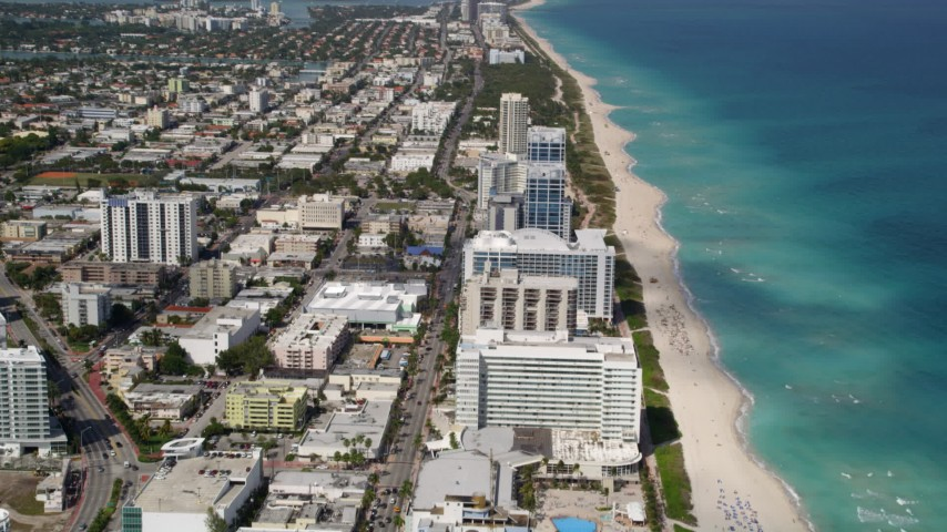 5K stock footage aerial video fly over beachfront skyscraper and tilt to wider view of the coast in Miami Beach, Florida Aerial Stock Footage | AX0020_062