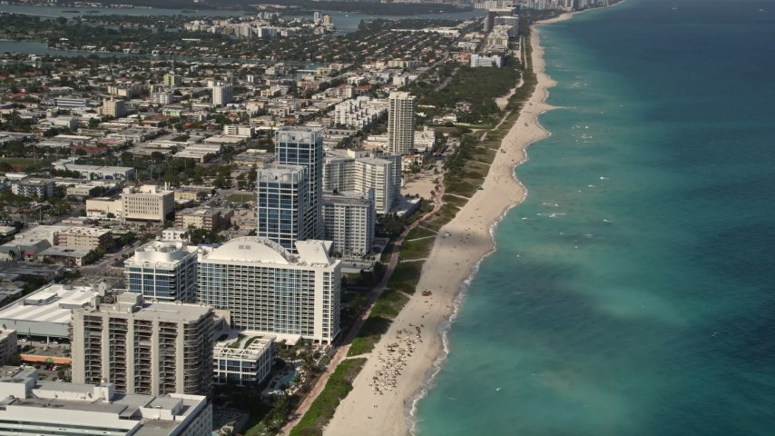 Flyby Beachfront Hotels and Tilt to Sunbathers in Miami Beach  Aerial Stock Footage | AX0020_063