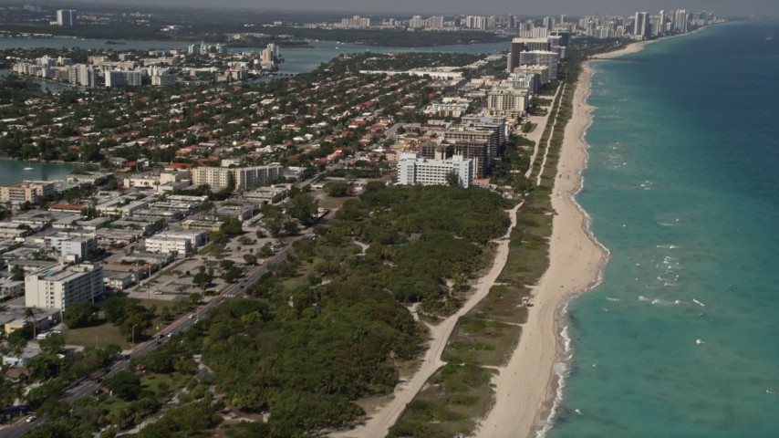 5K stock footage aerial video tilt from beachfront homes and park to reveal coastal hotels in Miami Beach and town of Surfside, Florida Aerial Stock Footage | AX0020_065