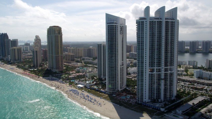 5K stock footage aerial video approach beachfront luxury resort hotel and tilt to sunbathers on the beach in Sunny Isles Beach, Florida Aerial Stock Footage | AX0020_082