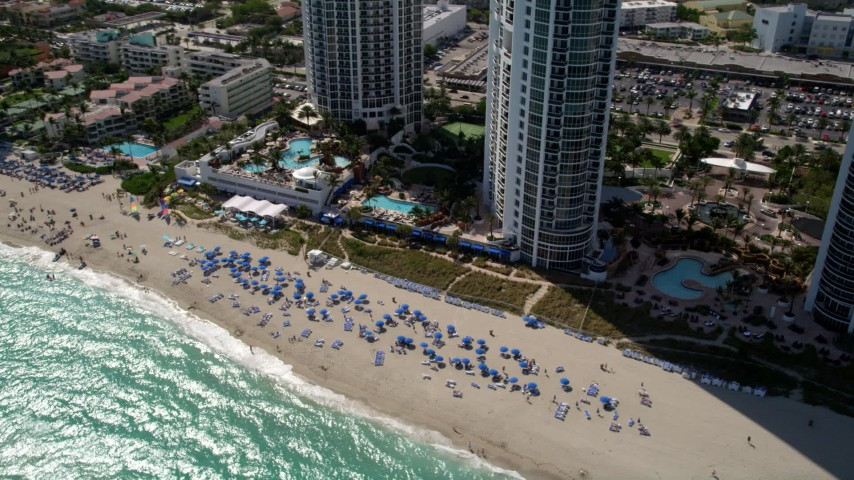 5K stock footage aerial video of sunbathers enjoying the beach at an oceanfront luxury resort hotel in Sunny Isles Beach, Florida Aerial Stock Footage | AX0020_083