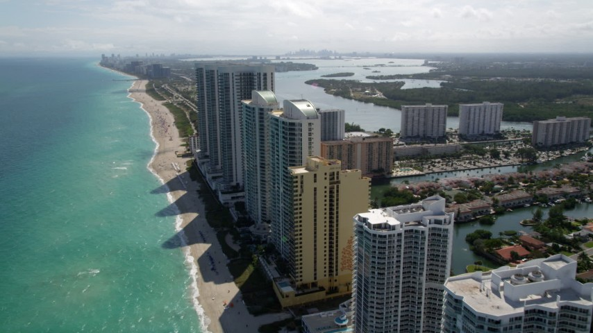 5K stock footage aerial video of oceanfront luxury condo high-rises by the beach in Sunny Isles Beach, Florida Aerial Stock Footage | AX0020_087