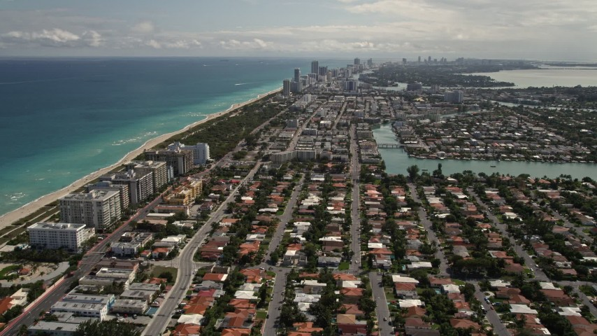 5K stock footage aerial video tilt up and fly over coastal residential neighborhoods in Surfside, Florida Aerial Stock Footage | AX0020_095