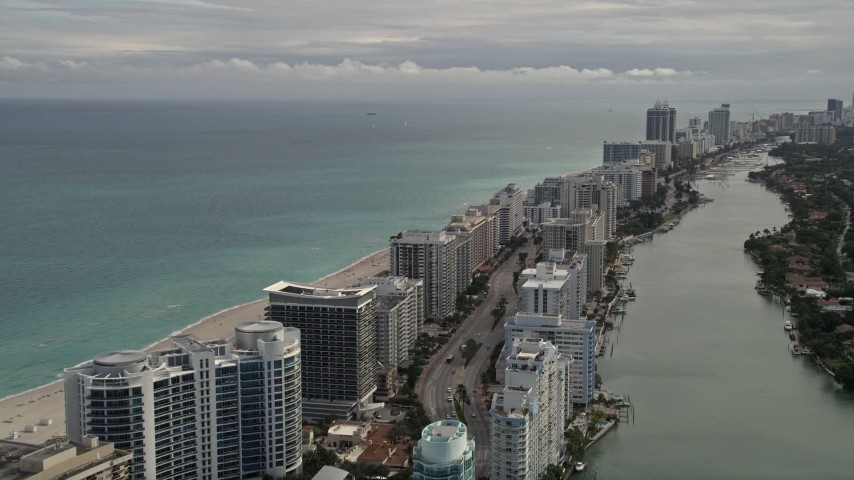 5K stock footage aerial video tilt from Indian Creek Drive to row of oceanfront condominiums in Miami Beach, Florida Aerial Stock Footage | AX0021_024