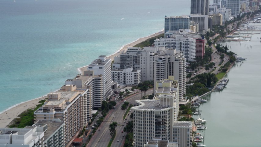 5K stock footage aerial video fly over beachfront condominiums on Collins Avenue in Miami Beach, Florida Aerial Stock Footage | AX0021_025