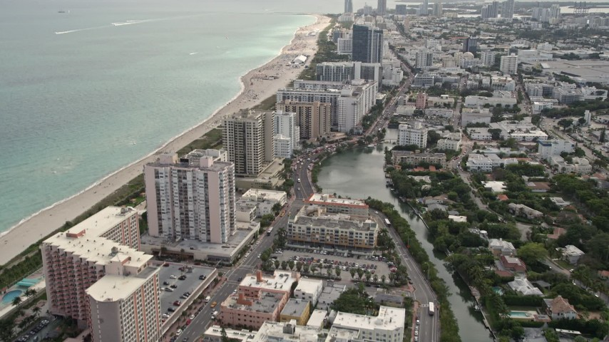 5K stock footage aerial video tilt from Indian Creek to reveal condominiums by the beach in Miami Beach, Florida Aerial Stock Footage | AX0021_034