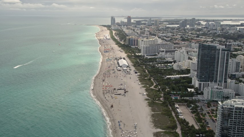 5K stock footage aerial video fly over beach to approach hotels and condominiums with ocean views in Miami Beach, Florida Aerial Stock Footage | AX0021_035E