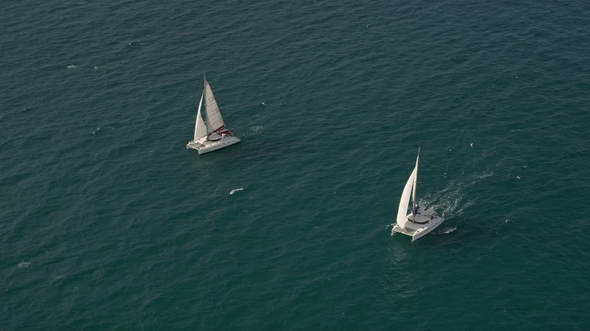5K stock footage aerial video tilt from calm ocean water to reveal and orbit two catamarans near South Beach, Florida Aerial Stock Footage   AX0021_037E