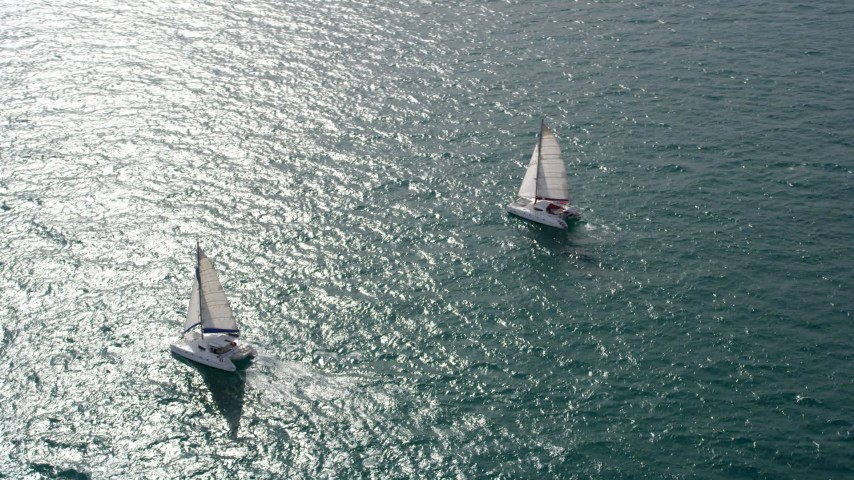 5K stock footage aerial video of an orbit of two catamarans on the ocean near South Beach, Florida  Aerial Stock Footage | AX0021_040