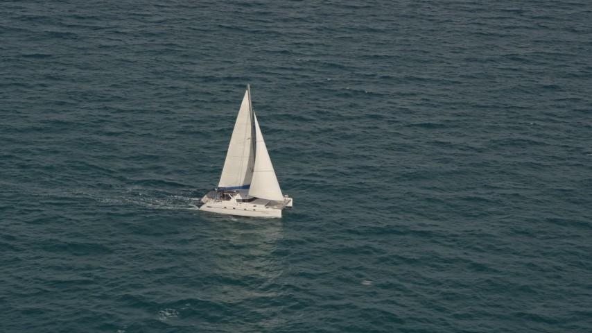 5K stock footage aerial video of catamaran sailing on the blue ocean near South Beach, Florida Aerial Stock Footage | AX0021_041E
