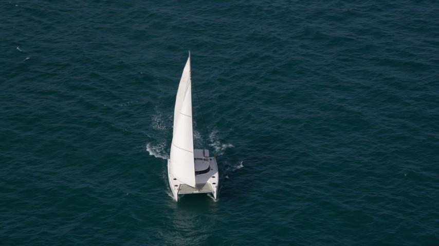 5K stock footage aerial video orbit of a catamaran sailing the ocean near South Beach, Florida Aerial Stock Footage | AX0021_042