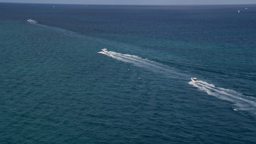 5K stock footage aerial video approach fishing boats racing across the blue water of the ocean near South Beach, Florida Aerial Stock Footage | AX0021_043
