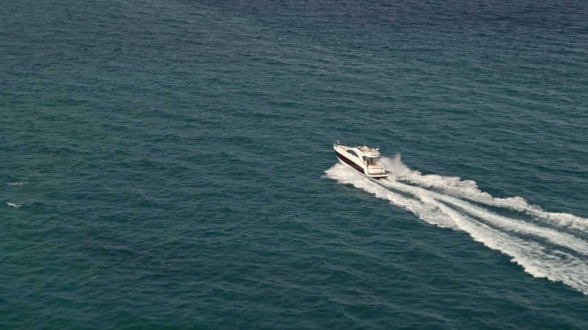 5K stock footage aerial video approach fishing boats racing across the blue water of the ocean near South Beach, Florida Aerial Stock Footage | AX0021_043E