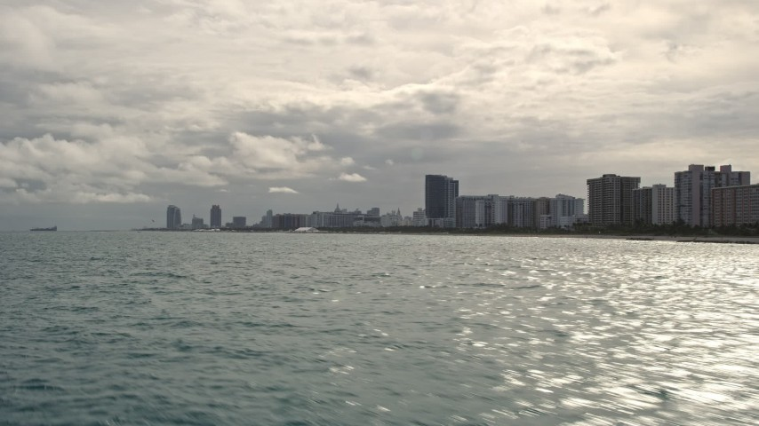 5K stock footage aerial video of low altitude view of oceanfront condos along the coast in Miami Beach, Florida Aerial Stock Footage | AX0021_048E
