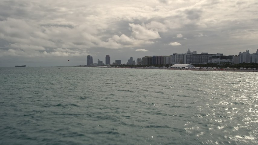 5K stock footage aerial video tilt from ocean to reveal oceanfront hotels and condos in Miami Beach, Florida Aerial Stock Footage   AX0021_050E