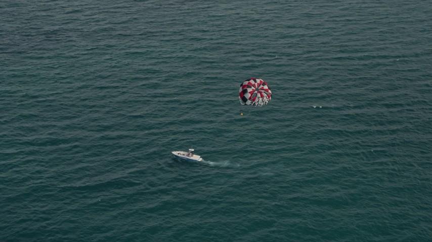 5K stock footage aerial video of parasailer gliding over the ocean near South Beach, Florida Aerial Stock Footage | AX0021_054E