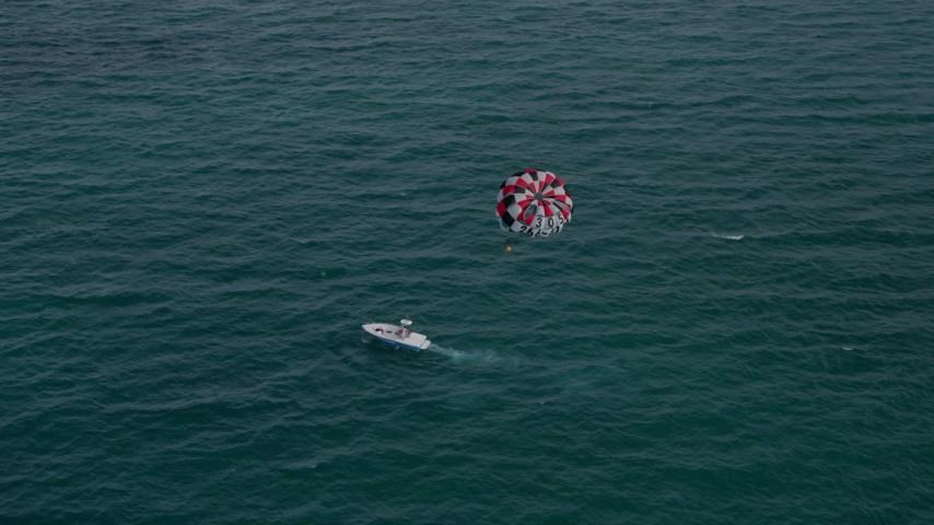 5K stock footage aerial video orbit parasailer gliding over the ocean near South Beach, Florida Aerial Stock Footage | AX0021_055