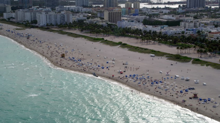 5K stock footage aerial video tilt down to people enjoying the beach in South Beach, Florida Aerial Stock Footage | AX0021_056
