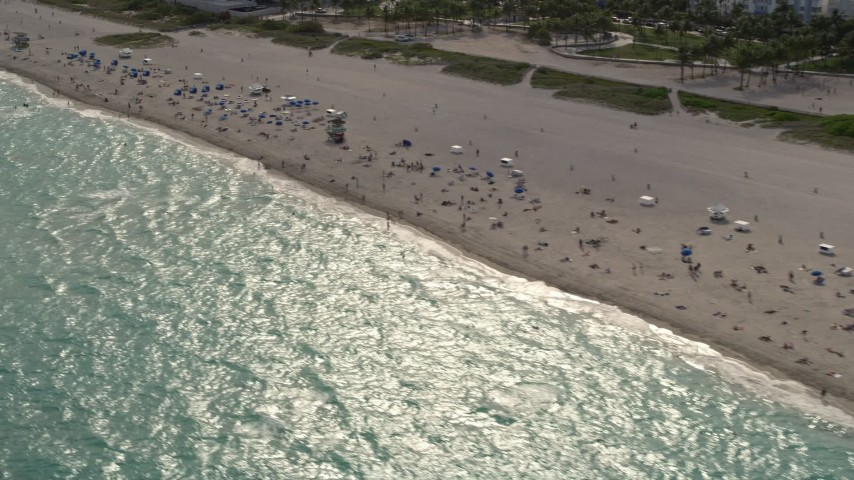 5K stock footage aerial video tilt down to people enjoying the beach by condos in South Beach, Florida Aerial Stock Footage   AX0021_056E