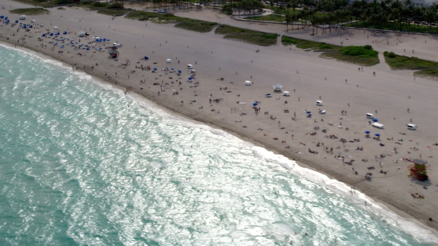 5K stock footage aerial video flyby people on the beach and in the water in South Beach, Florida Aerial Stock Footage | AX0021_057