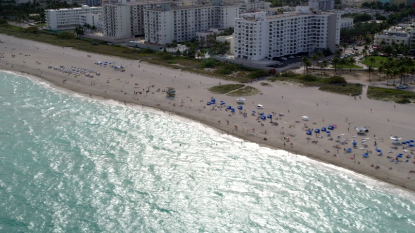 5K stock footage aerial video of passing people and beachside condos in South Beach, Florida Aerial Stock Footage | AX0021_058