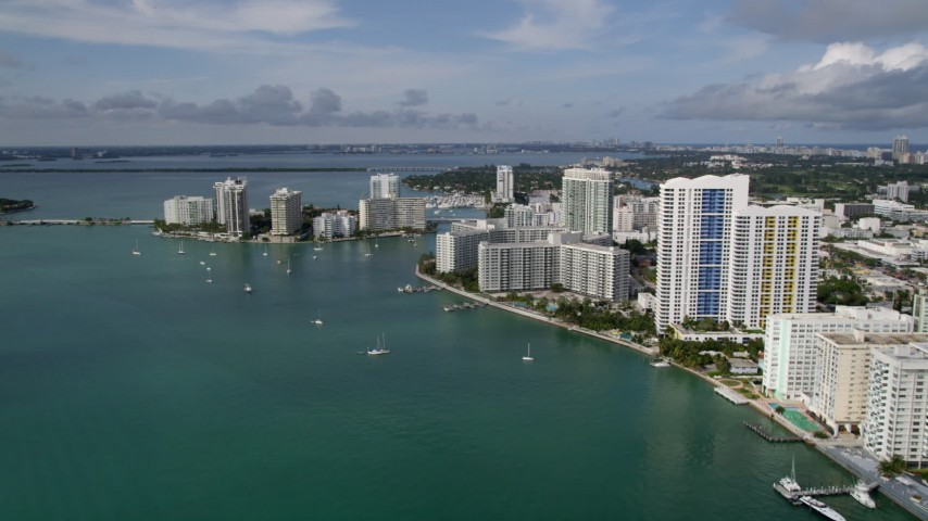 5K aerial video flyby waterfront South Beach condos and hotels to approach Belle Island, Florida Aerial Stock Footage | AX0021_065