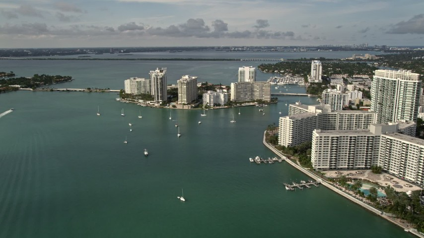 5K stock footage aerial video flyby waterfront South Beach condos and hotels to approach Belle Island, Florida Aerial Stock Footage | AX0021_065E