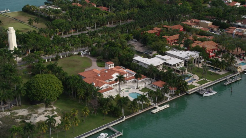 5K stock footage aerial video tilt from spacious waterfront mansion to wider view of Star Island, Florida Aerial Stock Footage | AX0021_071