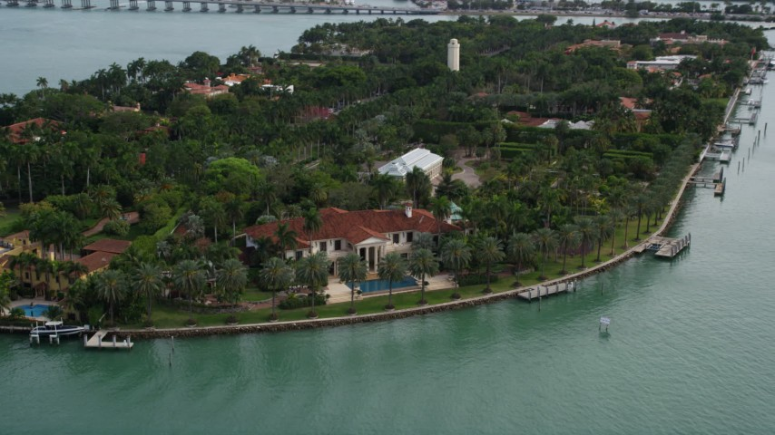 5K stock footage aerial video tilt from a spacious bayfront mansion to a wider view of Star Island, Florida Aerial Stock Footage | AX0021_073