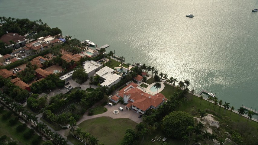 5K stock footage aerial video approach waterfront mansion and tilt to a bird's eye view of Star Island, Florida Aerial Stock Footage | AX0021_075