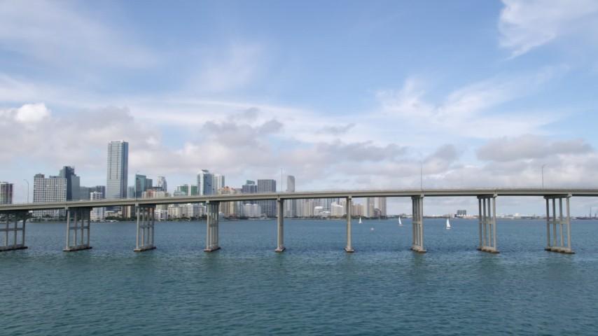5K stock footage aerial video flyby bridge on Rickenbacker Causeway to reveal Downtown Miami skyline, Florida Aerial Stock Footage | AX0021_113