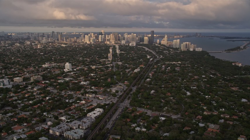 5K stock footage aerial video tilt from Coconut Grove suburbs to reveal Downtown Miami at sunset, Florida Aerial Stock Footage | AX0022_022