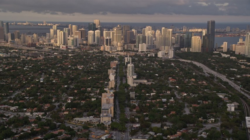 5K stock footage aerial video tilt from Coral Gables suburbs to reveal Downtown Miami at sunset in Florida Aerial Stock Footage | AX0022_023