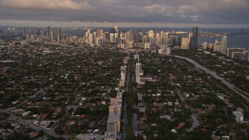 5K aerial video of following SW 3rd Avenue through suburbs to approach Downtown Miami at sunset, Florida Aerial Stock Footage | AX0022_024