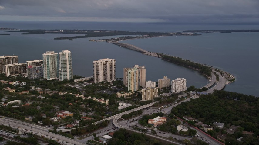 5K stock footage aerial video of waterfront condo complexes and the Rickenbacker Causeway in Downtown Miami at sunset, Florida Aerial Stock Footage | AX0022_025