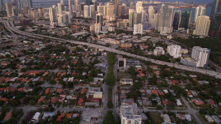 5K stock footage aerial video tilt from SW 3rd Avenue to reveal skyscrapers in Downtown Miami at sunset, Florida Aerial Stock Footage | AX0022_026