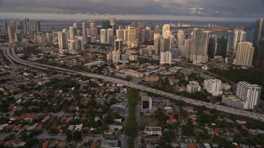 5K stock footage aerial video tilt from SW 3rd Avenue to reveal skyscrapers in Downtown Miami at sunset, Florida Aerial Stock Footage | AX0022_026E