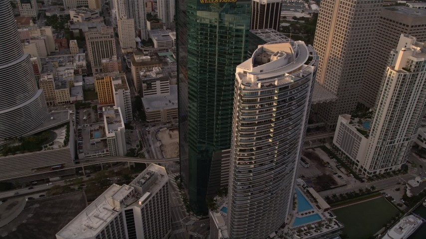 5K stock footage aerial video fly over modern high-rise to approach Epic Hotel and Wells Fargo Center in Downtown Miami at sunset, Florida Aerial Stock Footage   AX0022_030E