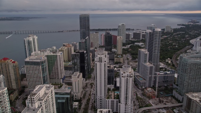 5K stock footage aerial video fly over Downtown Miami skyscrapers toward the Rickenbacker Causeway at sunset, Florida Aerial Stock Footage   AX0022_039E