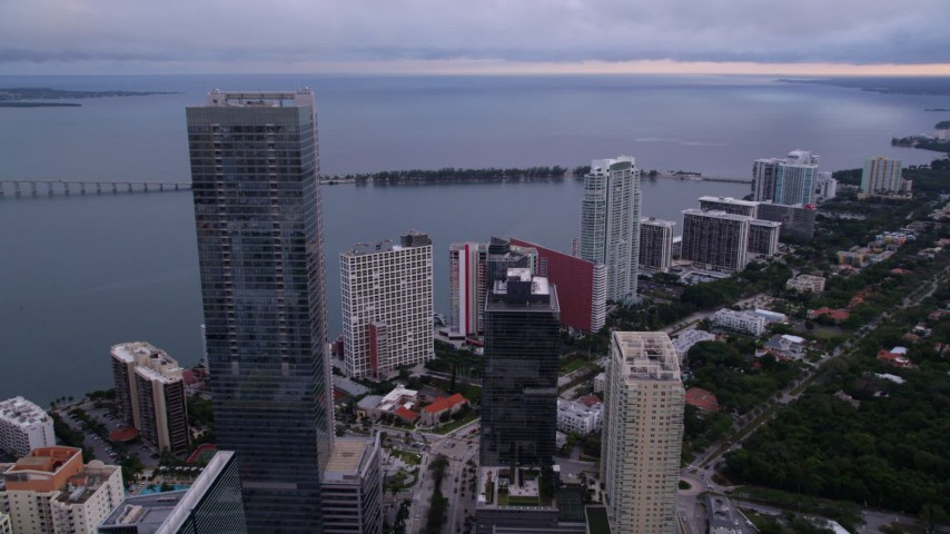 5K stock footage aerial video flyby the Four Seasons Hotel in Downtown Miami to approach Rickenbacker Causeway at sunset, Florida Aerial Stock Footage | AX0022_042