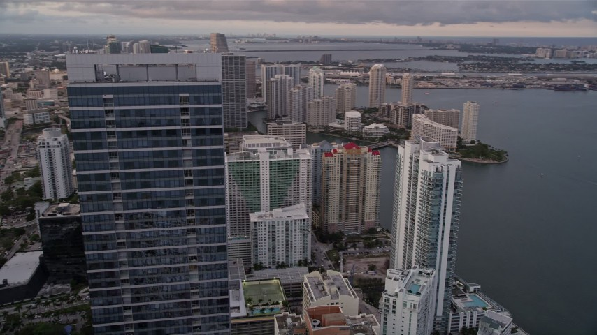 5K stock footage aerial video orbit top of Four Seasons Hotel to reveal waterfront skyscrapers in Downtown Miami at sunset, Florida Aerial Stock Footage | AX0022_043