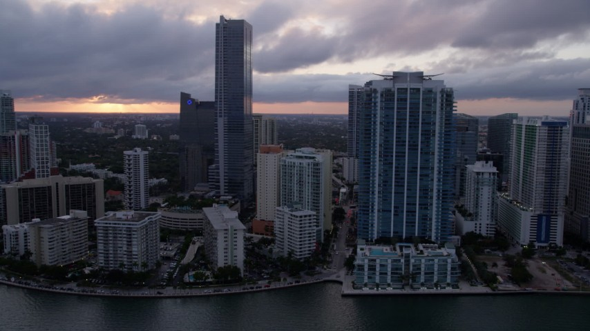 5K stock footage aerial video approach Four Seasons Hotel in Downtown Miami at sunset from Biscayne Bay, Florida Aerial Stock Footage | AX0022_058