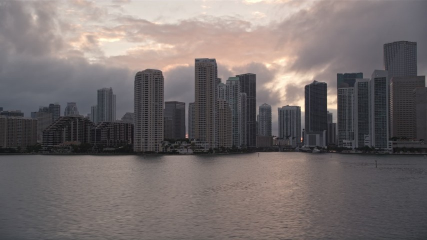 5K stock footage aerial video of Downtown Miami coastal skyline at sunset, approach Miami River, Florida Aerial Stock Footage | AX0022_061E