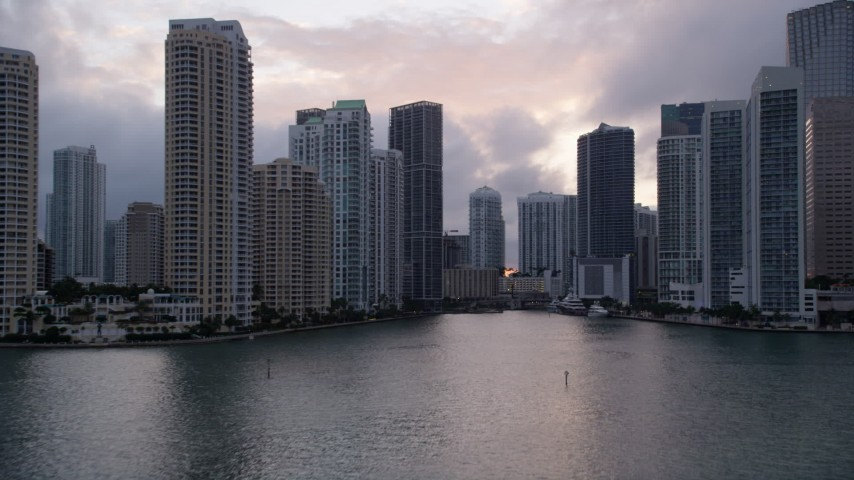 5K stock footage aerial video of low altitude approach to skyscrapers lining the Miami River in Downtown Miami at sunset, Florida Aerial Stock Footage | AX0022_063