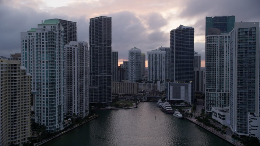 5K stock footage aerial video fly over Miami River to approach Icon Brickell in Downtown Miami at sunset, Florida Aerial Stock Footage | AX0022_064