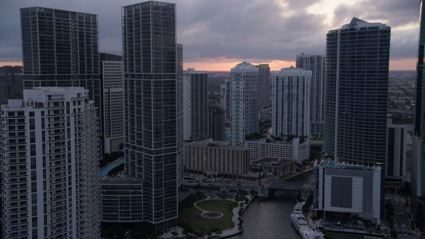 5K stock footage aerial video follow Miami River toward Icon Brickell and Brickell on the River in Downtown Miami at sunset, Florida Aerial Stock Footage | AX0022_065